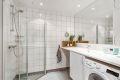 Baderom bestående av servantinnredning, innsvinbart dusjhjørne, vegghengt toalett og opplegg for vaskemaskin og tørketrommel.