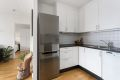 Kjøkken med integrert platetopp, komfyr og oppvaskmaskin.