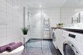 Flislagt bad med varmekabler på gulv, downlights i tak og opplegg for både vaskemaskin og tørketrommel under benkeplate.