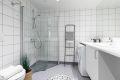 Flislagt baderom med varmekabler på gulv og downlights i tak. Det er opplegg for vaskemaskin og tørketrommel under benkeplate.