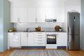 Kjøkken har hvite, slette fronter med stålhåndtak og flis over benkeplate.
