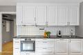 Kjøkken med lekre, profilerte fronter og integrert komfyr, platetopp og oppvaskmaskin.