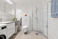 Flislagt baderom med varmekabler i gulv og downlights i tak. Det er opplegg for både vaskemaskin og tørketrommel.