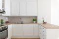 Lekkert og tidløst kjøkken med profilerte fronter og integrerte hvitevarer.