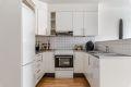 Kjøkken - glatte fronter, fliser over benkeplate og halvvegg mot stue