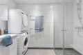 Lekkert flislagt baderom med opplegg vaskemaskin og tørketrommel som medfølger