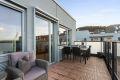 God plass til loungegruppe, blomsterkasser og grill på balkong.