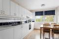 Kjøkkeninnredning med slette folierte fronter, laminat benkeplate m/fliser over, 1 1/2 oppvaskkum, ventilator og varmtvannsbreder i benkeskap.