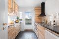 Nyere kjøkken med ventilator og integrert stekeovn, koketopp og oppvaskmaskin.