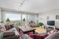 Stor og lys stue med store vindusflater som slipper inn rikelig med naturlig lys