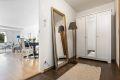 Entré med garderobeskap. Flislagt gulv og lysmalte veggflater. Her er det god plass til yttertøy og sko.