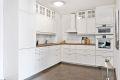 Funksjonelt og lekkert kjøkken med rikelig skap- og benkeplass. Innredning med profilerte formpressede fronter med flere glasskap og en pen laminat benkeplate med tidsriktige fliser over.