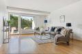 Lys fin stue med utgang til terrassen. Store vindusflater.