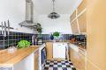 Klassisk kjøkkeninnredning med opplegg for oppvaskmaskin og fliser over benk.