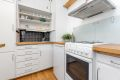 Kjøkken med original eldre innredning og heltre benkeplate.