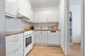 Kjøkkeninnredning med laminat benkeplate, komfyr, ventilator og opplegg for oppvaskmaskin.