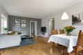 En romslig stue med god plass til både sofagruppe og spisebord.