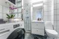 Flislagt bad/wc består av dusjplass m/ dør, servant med skapinredning, wc og opplegg for vaskemaskin.