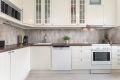 Hvit laminert kjøkkeninnrending, laminert benkeplate og fliser over kjøkkenbenk.