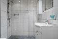 Badet fremstår lyst og moderne med lyse fliser på vegg og gulv, hvit baderomsinnredning og downlights i tak.