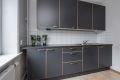 Kjøkkenet har grå fronter med grå benkeplate og hvite fliser på bakvegg. Her har man godt med både benkeplass- og lagringsplass!