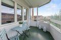 Innglasset balkong med skyveglass. Utsikt til store grøntområder som er pent stelt.
