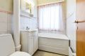 Praktisk bad, i dag er det badekar, servant nedfelt i innredning, skap med speil i front og toalett.