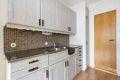 Kjøkken med laminat på gulv, malte strirer på vegger og malt tak.