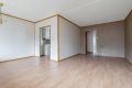 Romslig stue med laminat på gulv, tapet og tekstilstrier på vegger og malt tak.