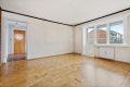 Romslig stue med parkett på gulv, tekstilstrier på vegger, 1 vegg med teglstein og malt tak.
