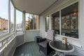 7 kvm innglasset balkong. Treplatting. Panelt vegg inn mot vindu og dør med utebelysning.