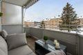 Solrik balkong med treplatting, utebelysning, glassvegger som skjermer fra sidene og fritt utsyn.
