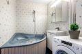 Bad med badekar, servant nedfelt i innredning. Opplegg for vaskemaskin.