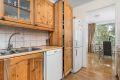 Oppvaskmaskin, nisje til kjøleskap. Fliser over kjøkkenbenk.