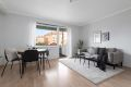Stue med laminat på gulv og malte veggoverflater.
