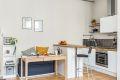 Kjøkkenøyløsningen gir både ekstra benkeplass og sittemuligheter, og skaper et skille mellom kjøkken og sittegruppe.