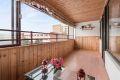 Stor, solrik og innglasset balkong med utsikt mot fellesarealene.
