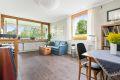 Romslig stue med store vinduer som slipper inn rikelig med naturlig dagslys