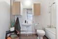 Eldre bad som består av dusjplass i badekar, servant, speil, overskap, opplegg for vaskemaskin og wc.