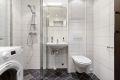 Fint fliselagt baderom bestående dusjhjørne, servant, speil med overlys, opplegg til vaskemaskin og vegghengt wc.