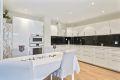 Nytt kjøkken med innredning i hvit høyglans. Integrert oppvaskmaskin, stekeovn, mikrobølgeovn, induksjon koketopp, samt kjøl- og fryseskap