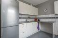 Kjøkken i hvit slett utførelse med fliser over benk