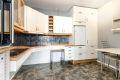 Kjøkkeninnredning med slette lakkerte fronter, 2 stk. fronter med glass, laminat benkeplate, dobbel oppvaskkum, uttrekksventilator og opplegg for oppvaskmaskin.