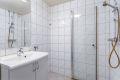 Badet består av dusjhjørne, servant med underskap, speil med lys ig vegghengt klosett.
