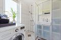 Flislagt bad med varmekabler pusset opp i regi av borettslaget. Opplegg for vaskemaskin.