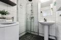 Pent, flislagt baderom med elektrisk gulvvarme. Badet er utstyrt med hvit glatt servant på søyle, speil og lysarmatur på vegg over servant. Dusjhjørne med glassdører for optimal plassutnyttelse og opplegg for vaskemaskin.