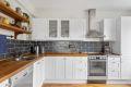 Kjøkkeninnredning med malte, profilerte fronter med vitrinedører. Nedfelt kjøkkenbeslag i heltre benkeplate. Fliser over benk.