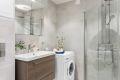 Baderommet inneholder: dusjhjørne med regnfalldusj og to svingbare dusjdører, vegghengt toalett, høyskap med glatte, folierte fronter, heldekkende servant med underskap, speilskap med lysarmatur. Opplegg til vaskemaskin.