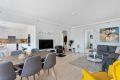 Lys og tiltalende stue med malte glatte flater og pene parkettgulv.