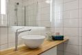 Pent, flislagt bad/wc med varme i gulv. Et godt sted å starte dagen! Servant på benk over skapinnredning, i tillegg til hyller gir gode lagringsmuligheter for toalettartikler, mm.